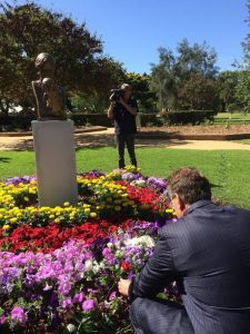 Ted Baillieu placing a rose at the base of the memorial statue of Mother and Child